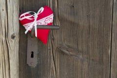 Forme rouge de coeur accrochant sur la poignée de porte ou un fond en bois, c Images libres de droits