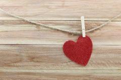 Forme rouge de coeur accrochant sur une corde de chanvre sur le fond en bois brun Images stock