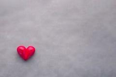 Forme rouge de coeur avec l'arc sur le fond gris noir ` S de Valentine Images libres de droits