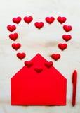 Forme rouge de coeur avec l'enveloppe et le stylo sur le fond en bois Image libre de droits