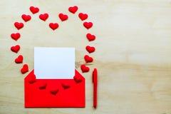 Forme rouge de coeur avec l'enveloppe et le stylo sur le fond en bois Photo stock