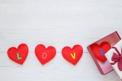 Forme rouge de coeur avec le mot d'amour dans le boîte-cadeau avec le ruban sur le blanc Photos stock