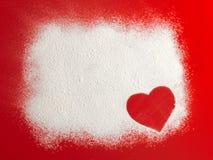 Forme rouge de coeur d'amour de Valentine dans la neige sur le fond rouge Image stock