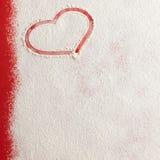 Forme rouge de coeur d'amour de Valentine dans la neige sur le fond rouge Images libres de droits