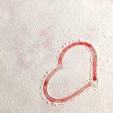 Forme rouge de coeur d'amour de Valentine dans la neige sur le fond rouge Image libre de droits