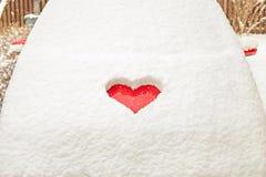 Forme rouge de coeur d'amour de Valentine dans la neige sur le capot rouge de voiture Photos libres de droits