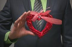 Forme rouge de coeur dans des mains d'homme d'affaires Cadeau de l'amour Amour actuel Photographie stock libre de droits