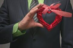 Forme rouge de coeur dans des mains de monsieur Cadeau de l'amour Amour actuel Photographie stock