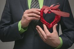 Forme rouge de coeur dans des mains de monsieur Cadeau de l'amour Amour actuel Images stock