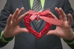 Forme rouge de coeur dans des mains de monsieur Cadeau de l'amour Amour actuel Photographie stock libre de droits