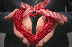 Forme rouge de coeur dans des mains de monsieur Cadeau de l'amour Amour actuel Images libres de droits
