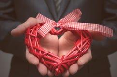 Forme rouge de coeur dans des mains de monsieur Cadeau de l'amour Amour actuel Photos stock