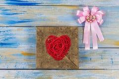 Forme rouge de coeur de perle de fil sur le cadre en bois d'or avec la goupille Photos stock