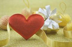 Forme rouge de coeur de tissu avec le boîte-cadeau sur le fond d'or, concept d'amour Image libre de droits
