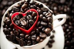 Forme rouge de coeur sur des grains de café Image libre de droits