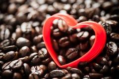 Forme rouge de coeur sur des grains de café Images stock