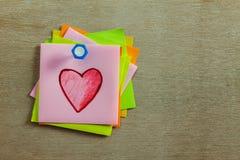 forme rouge de coeur sur la note et la cheville collantes colorées sur le backgrou en bois Photos libres de droits