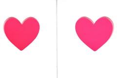 Forme rouge de deux coeurs coupée dans le conseil en bois blanc Photo stock