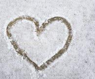 Forme tirée par la main de coeur dans la neige sur le grès Images libres de droits