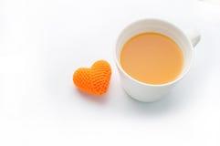 Forme tricotée de coeur de tissus et jus d'orange d'isolement sur b blanc Images stock