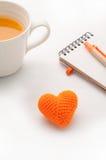 Forme tricotée de coeur de tissus, papier de note et isolat de jus d'orange Photo stock