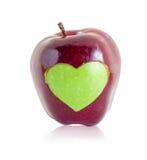 Forme verte de coeur de pomme dans la pomme rouge Images stock