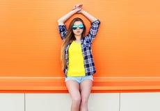 Forme a vestir bonito da menina óculos de sol e short na cidade sobre colorido foto de stock