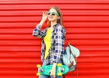 Forme a vestir bonito da menina óculos de sol, skate Imagem de Stock