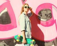 Forme a vestir bonito fresco da menina óculos de sol, calças de brim camisa e skate Fotografia de Stock