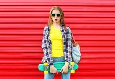 Forme a vestir consideravelmente fresco da menina óculos de sol, skate Imagem de Stock