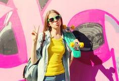 Forme a vestir consideravelmente fresco da menina os óculos de sol e o skate que têm o divertimento na cidade sobre colorido Fotografia de Stock