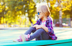 Forme a vestir da criança óculos de sol e o assento quadriculado da camisa imagem de stock