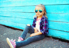 Forme a vestir da criança óculos de sol e o assento quadriculado da camisa foto de stock royalty free
