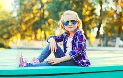 Forme a vestir da criança da menina óculos de sol e a camisa quadriculado fotos de stock