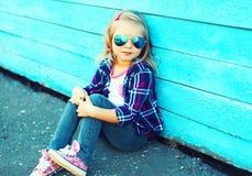 Forme a vestir da criança da menina óculos de sol e a camisa quadriculado imagem de stock