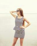 Forme a vestir da jovem mulher óculos de sol e o vestido listrado imagem de stock