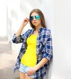 Forme a vestir da moça do retrato óculos de sol e a camisa quadriculado foto de stock