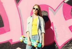 Forme a vestir fresco da menina óculos de sol, calças de brim camisa e skate Imagens de Stock