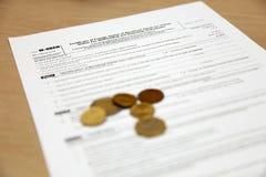 Forme W8BEN com moedas Imagem de Stock Royalty Free