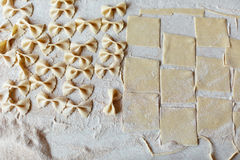 Formed pasta on table. From above dough and formed farfalle pasta on table Royalty Free Stock Photo