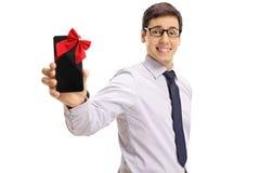 Formeel geklede kerel die die telefoon tonen met lint als gift wordt verpakt Stock Foto's