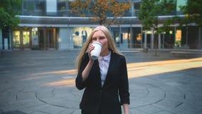 Formell kvinna som dricker kaffe i uteplats Elegant blond kvinna i dräkt och med långt hår som in dricker kaffe från den vita kop arkivfilmer