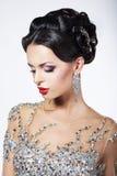 Formellt parti. Ursnygg modemodell i ceremoniell skinande klänning med juvlar Royaltyfri Fotografi