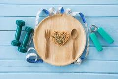 Formen Sie das Herz, das vom ganzen Korn auf hölzernem Teller gemacht wird Stockbild