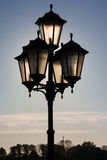 Former Black Lantern. Street lantern on a black background of a sunset, blue sky Stock Photography