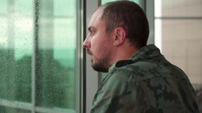 Former military man stands by the window, it is raining stock footage