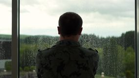 Former military man stands by the window, it is raining stock video footage