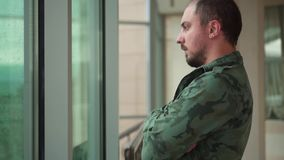 Former military man stands by the window, it is raining stock video