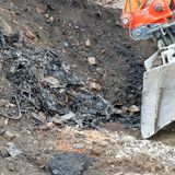 Former rubbish dump in the excavation pit, black discoloured and Stock Image