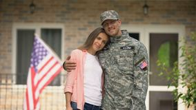 Former soldier and girlfriend hugging, standing against USA flag, homecoming. Stock footage stock video